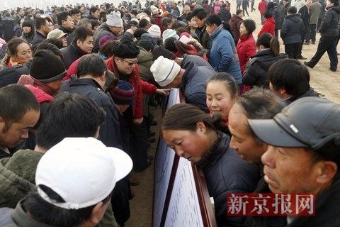 当地村民围在机场规划图前观看。新京报记者 周岗峰 摄