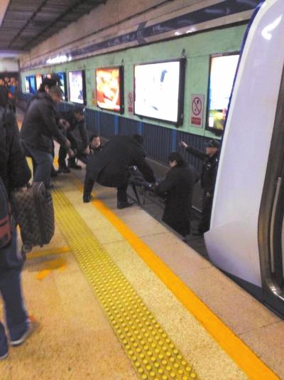 地铁工作人员将林某从站台下救起。网友供图
