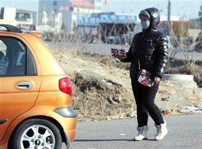 """12月22日,唐山市公安局交通警察支队车辆管理所二分所门口,一名代办人员拿着""""验车""""的牌子,在车流间招揽生意。"""
