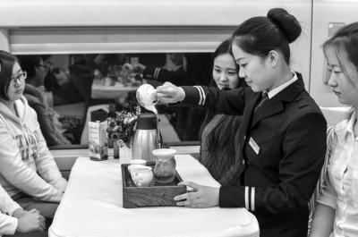 茶艺师在餐车内为游客沏茶。