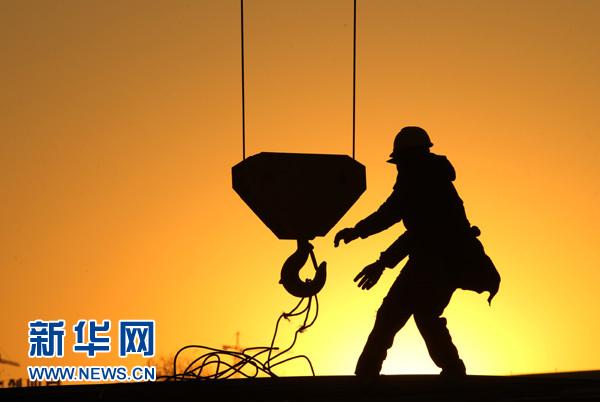 2015年1月1日,工人在江苏省南通市一处保障房施工现场吊运钢筋。新年第一天,众多劳动者在元旦假期坚守在工作岗位上。 新华社发(许丛军 摄)