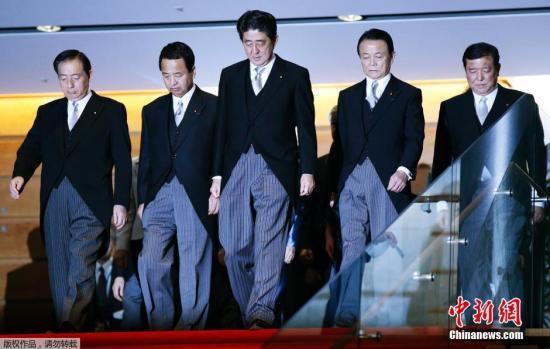 资料图:当地时间2014年12月24日,日本东京,日本首相安倍晋三及其新一届内阁成员在首相官邸拍摄合影。