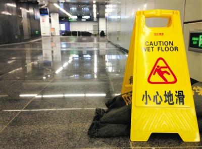 昨日中午,地铁14号线东湖渠站,漏水处摆放着沙袋及警示牌。因上方污水管被挖断,积水渗入地铁站。实习生 彭子洋 摄
