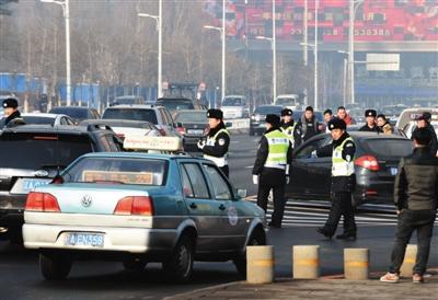 1月4日,警察在沈阳街头疏导出租车。新华社记者 杨青 摄