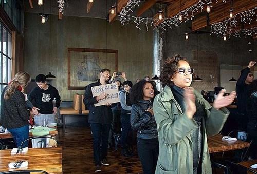 视频截图:30多名手持标语,高呼口号的抗议者闯入餐馆,要求在场顾客全部起立和他们一起挥拳,反对警察的暴力执法,为被打死的非洲裔平民伸张正义。
