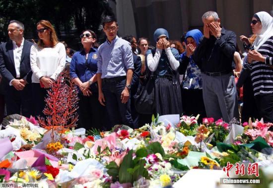 资料图:当地时间2014年12月16日,澳大利亚悉尼,澳大利亚总理阿博特夫妇前往马丁广场亲自献花,悼念悉尼咖啡馆人质劫持事件死难者。
