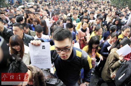 资料图:在南京林业大学公务员笔试考点,一名考生举着准考证进入考场。新华社发(刘建华 摄)