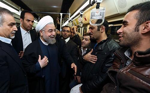 图为鲁哈尼等伊朗政府要员在地铁上与民众交谈。