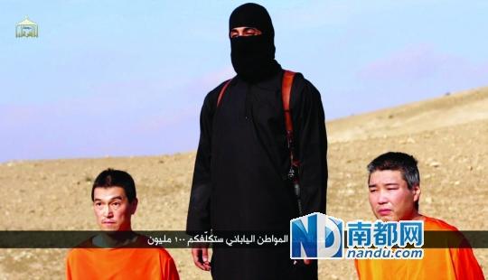 """1月20日公布的视频截图显示两名日本人质跪在手持匕首的""""伊斯兰国""""极端组织成员(中)旁边。"""