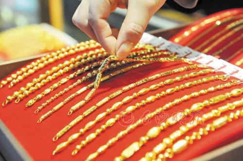 最近的国际金价大幅上涨,亦推升国内金饰品价格。图为一家金店的店员在整理黄金饰品。 新华社发