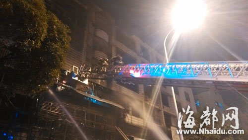 消防人员通过云梯进入民房内搜救