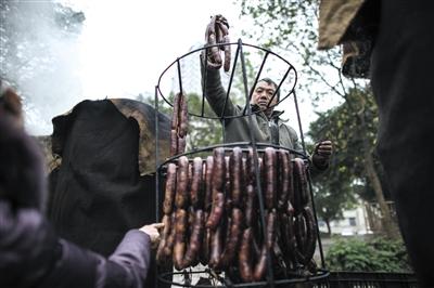 2014年12月30日8时许,重庆巴南区毛纺厂,居民将风干的香肠挂上熏架。每年这时候,居民们就会熏制香肠、腊肉、排骨等过年食物。图/东方IC