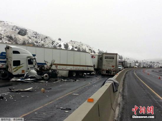 """当地时间2015年1月17日,一股致命的""""闪冻""""风暴正席卷了宾州、新泽西和纽约的大部分地区,造成大量州际公路交通堵塞,图为俄勒冈贝克城附近的州际公路84号上,超过12辆拖车在冰滑路面撞车,导致12人受伤。"""