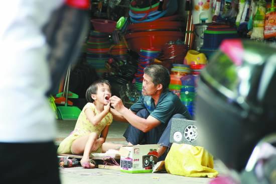 2012年6月26日,海南省三亚市,小飞燕及其养父王军在行乞。CFP供图