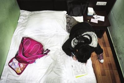 曹莹趴在宾馆的床上做作业