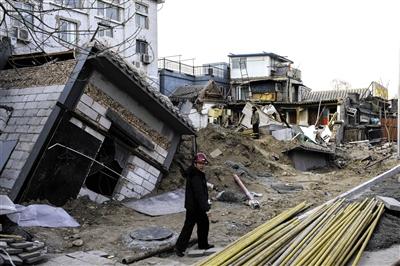 昨日,德内大街因违建地下室而倒塌的几间民房处,工作人员准备用钢材暂时支撑受损房屋。 新京报记者 周岗峰 摄