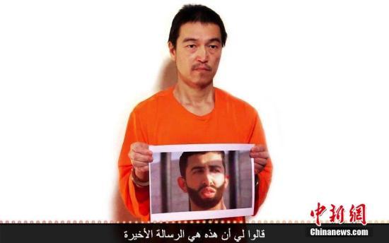 """2015年1月28日消息,美国视频网站YouTube于27日出现疑是极端组织""""伊斯兰国""""(ISIS)发布的新威胁,图像显示日本人质后藤健二手持被俘的约旦飞行员卡萨斯贝的照片,称自己""""只剩24小时"""",而留给约旦飞行员的时间更短。图像中,后藤健二戴着手铐,仍穿着橙色衣物,举着一张疑是卡萨斯贝的照片。CFP视觉中国"""