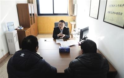接谈室内,两名来访人员正在与工作人员接谈。