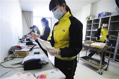 工作人员戴着手套和口罩处理群众来信。