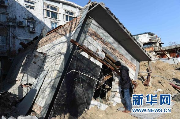 1月28日,一名工作人员在北京市德内大街93号院塌陷现场查看倒塌的建筑。新华社记者 罗晓光