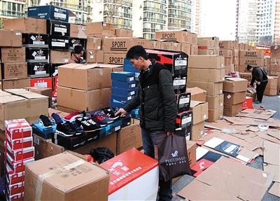 昨日,百荣商城2期地下鞋城百余商户,将因灭火被浸泡的鞋子拿到停车场上晾晒并降价出售。 实习生 彭子洋 摄