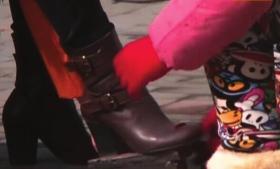 玲玲在小区门口给一位女士擦鞋。