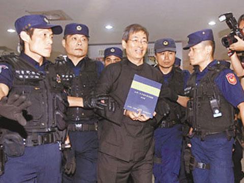 2013年6月29日,张安乐(中)回到台湾后被警察押往地检署(资料图)