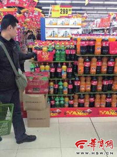 2月9日,西安市大庆路一家大型超市里,一市民从饮料区走过