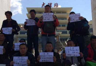 大理火车站,没钱买车票的民工们举牌向好心人寻求帮助。