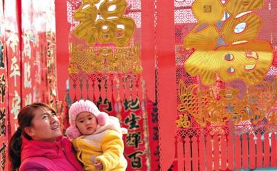 2月15日,一名密斯带着小孩在怀柔的年货商场选购节庆饰品。新华社发(卜向东 摄)