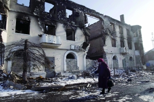 在乌克兰东部,一名女子走过被毁的楼房。新华/路透