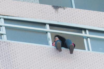 28楼的窗台上坐着一名女子,其两条腿耷拉在室外,不停地摆动。