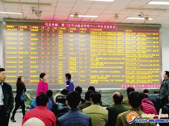 图为求职者在厦门市人力资源市场信息滚动屏前细细筛选招聘信息。记者 吴斯婷 摄