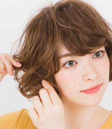 step2,从头顶部位取出一小束头发,用卷发棒将这束头发烫出卷度,然后再图片