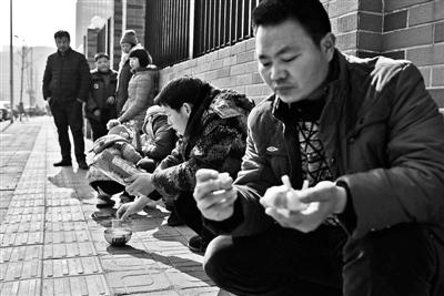 孩儿们和家长在路边就着大蒜吃午餐