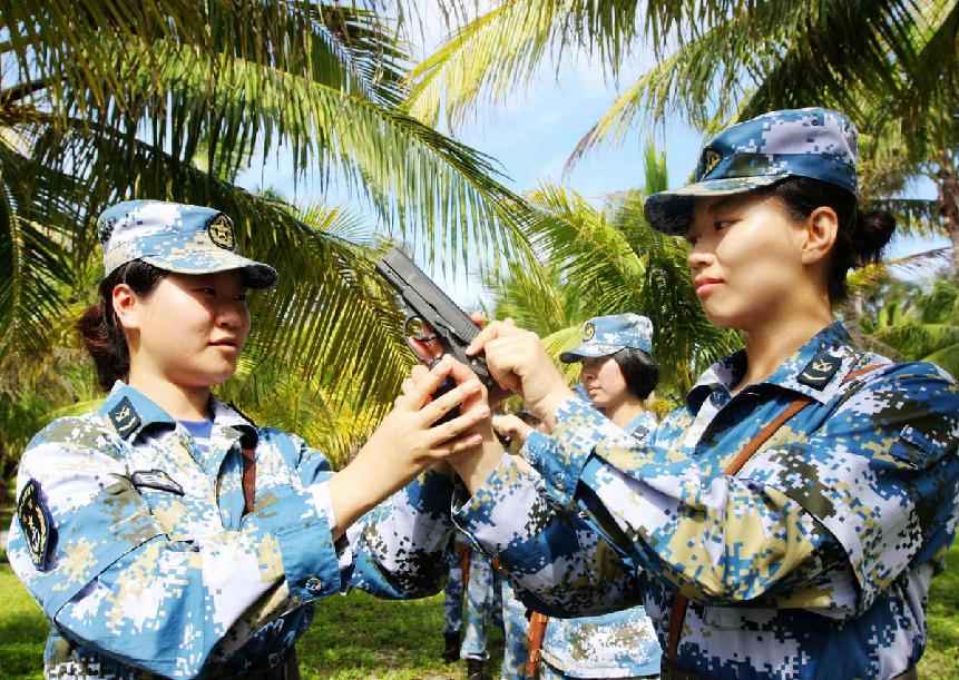 """3月8日,西沙女兵刻苦练习端枪臂力。3月的西沙海岛已烈日炎炎,南海舰队某水警区通信连女兵正在进行刻苦训练,她们用实际行动迎接""""三八""""妇女节的到来。新华社发(赵向虎 摄)"""