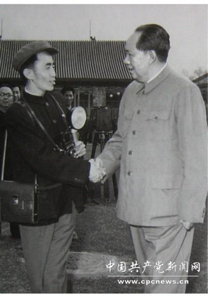 1958年,吕厚民手拿闪光灯、相机、挎包和毛主席握手。