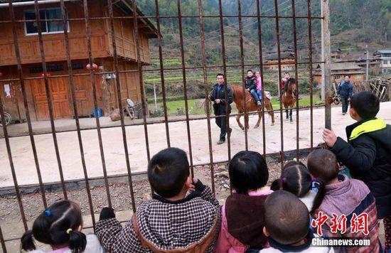 3月10日,广西桂林木洞山屯,在经过约1.5小时后,三名孩子终于走到了学校。尽管每天上学都是骑马而来,但每次同学们都觉得好看,都来校门口围观。刘教清 摄 CFP视觉中国