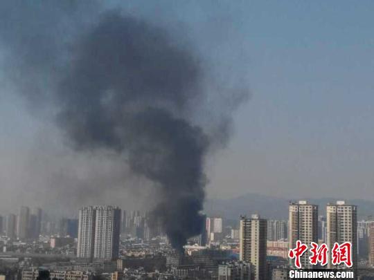 图为火灾导致市区上空黑烟滚滚 补平 摄