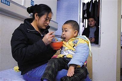 李艳菊抱着小宇航喂他吃排骨,为了孩儿,周刚佳耦只茹素菜,把省下的钱给儿子增强养分。
