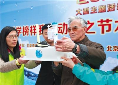 """昨天,旭日十里堡北里社区,""""北京典范""""金九皋白叟向住民展现他创造的马桶节水安装。 练习生 彭子洋 摄"""