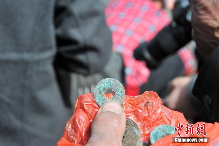 """3月21日上午,盐城市盐都区龙冈镇一清理河道的工地上,大型挖掘机挖出了一堆铜钱,周围许多村民闻讯后纷纷赶来挖掘""""淘宝""""。据不完全统计,挖出的铜钱有两三百斤重。博物馆考古专家到现场后,发现铜钱都是唐宋时期的古钱币,属于文物,于是联系当地派出所及时对现场进行了保护。"""