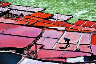 当地群众在澜沧江畔开山凿井,取出岩层深处含盐的卤水倒入盐田,经阳光