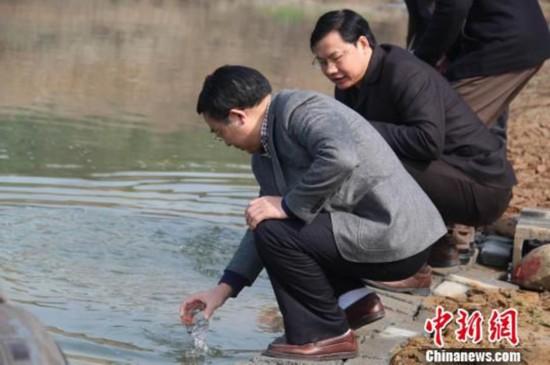 荆门市副市长张尚贵(左一)和英博金龙泉啤酒湖北公司总司理谢模志(左二)现场舀水直饮。吴奇勇摄