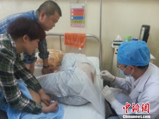 图为被打致伤的胡瑞正在承受腰椎穿刺审查。 胡贵龙 摄