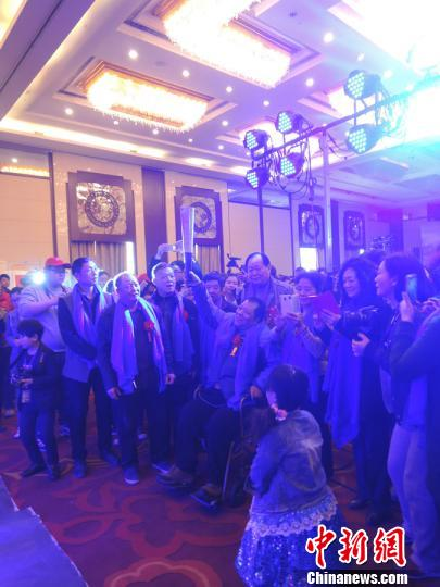 """在爱心人士的接力传递下,象征希望之火的""""蓝梦火炬""""传递到郑州市陇海大院居民手中,高位截瘫的高新海在志愿者和邻居们的簇拥下高高举起火炬,点燃蓝色火焰,开幕式现场成为蓝色的海洋。 赵晖 摄"""
