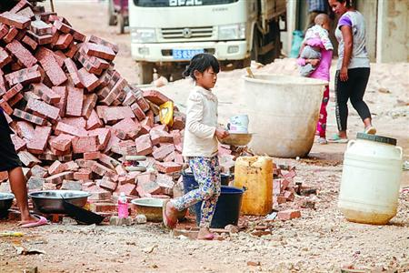 缅甸境内的难民营,一个女孩拿着洗净的餐具在其中穿行。