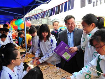 图为清华附中王殿军校长与学生互动体验科学游戏