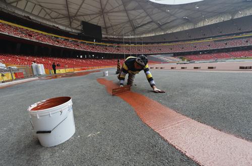 ▲为了保证施工质量,工作人员跪在赛道上工作