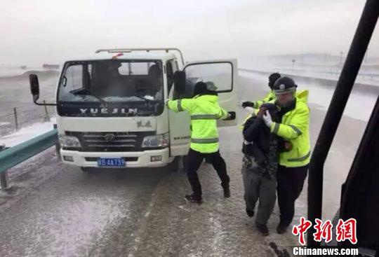 4月1日,新疆乌鲁木齐至吐鲁番三十里风区微风,交警帮忙救济被微风围困职员。 交警供给 摄